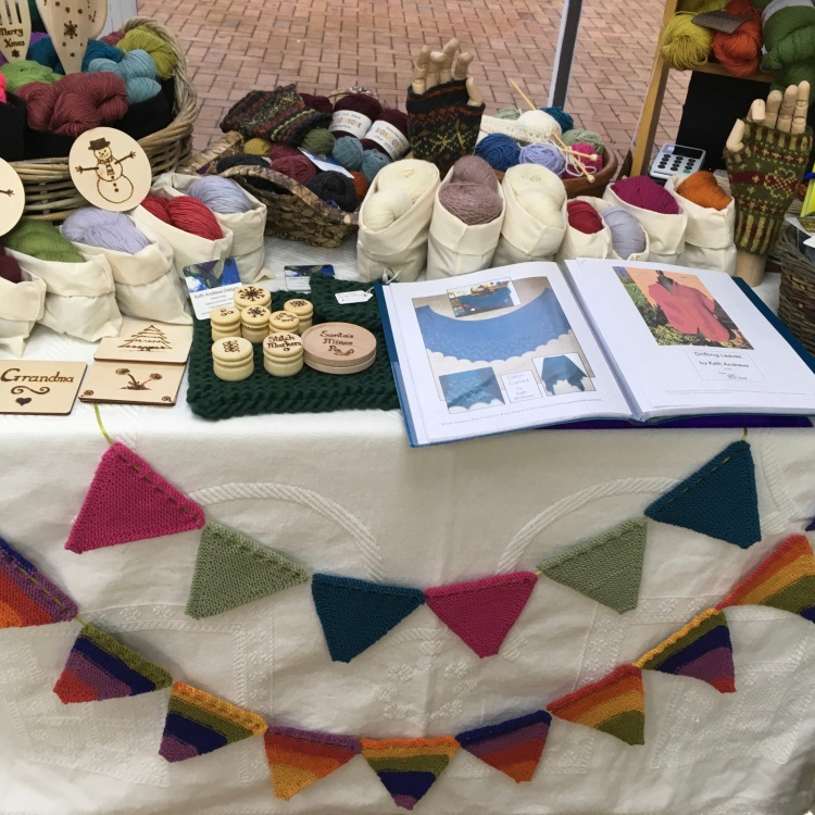 A picture of my stall at the pop-up shop, with bunting, wooden treats, and knitting kits. Open on the table is my portfolio of patterns.