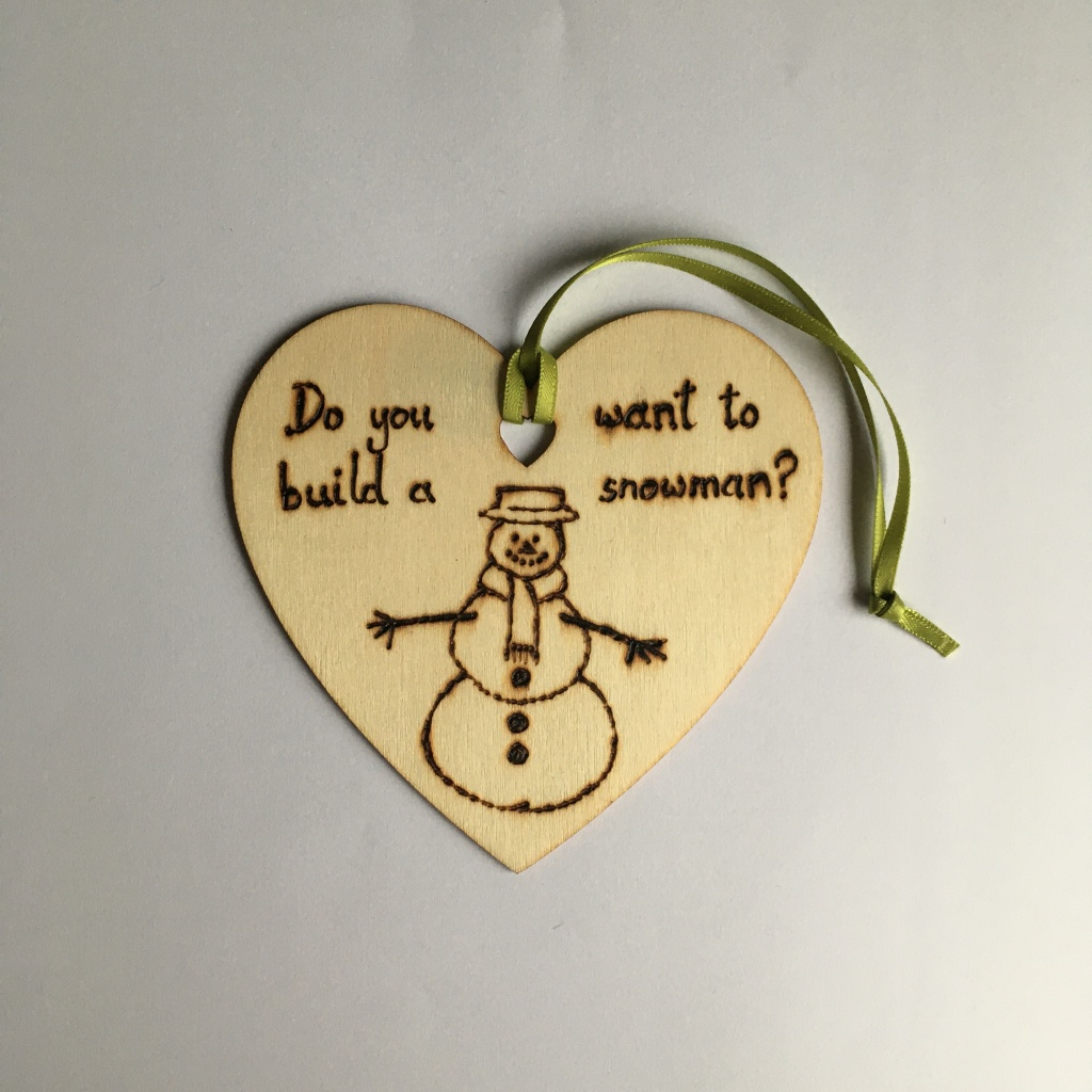 A picture of a hanging heart decoration with the words 'Do you want to build a snowman?' and a picture of a snowman wearing a hat and scarf burnt onto it.