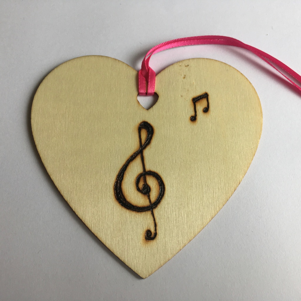 A picture of a hanging heart decoration with a large treble clef and a small pair of quavers burnt onto it.
