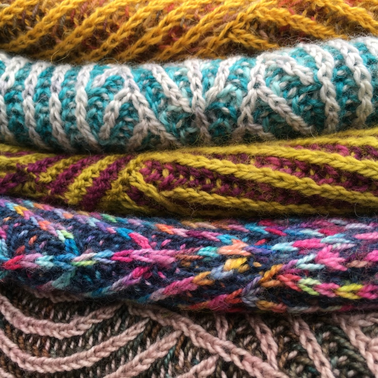 A picture of all five of the brioche shawls stacked together.