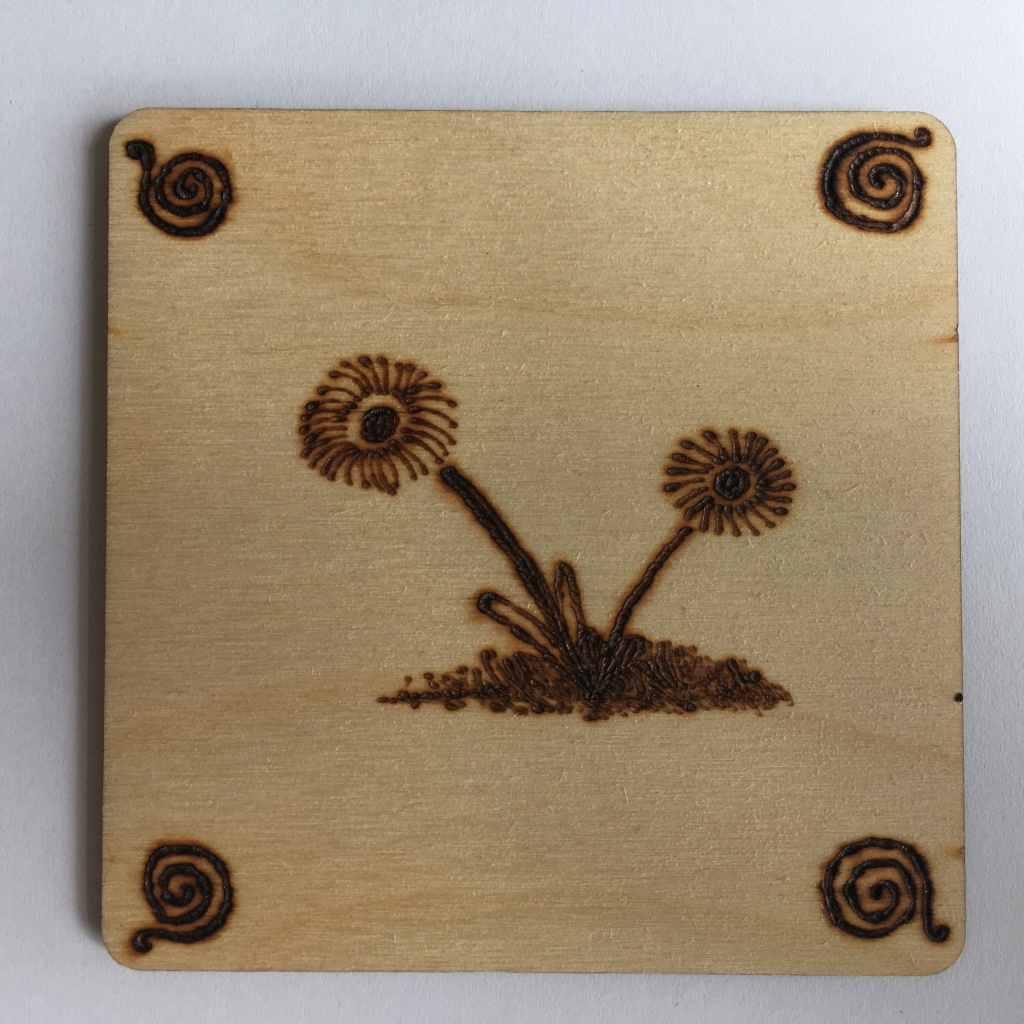 A picture of a square coaster with a pair of daisies in a grassy mound burnt onto it. There is a small swirl in each corner.
