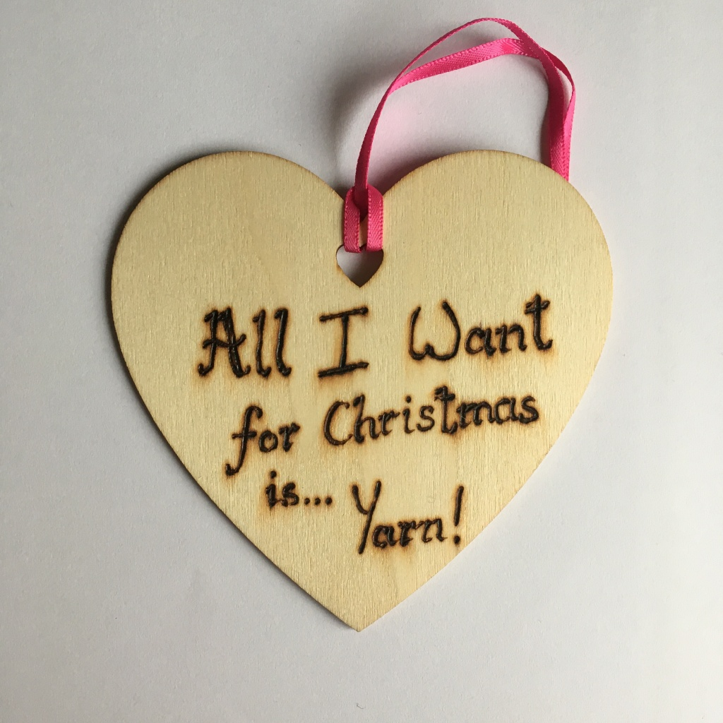 A picture of a hanging heart decoration with the words 'All I want for Christmas is...Yarn!' burnt onto it.