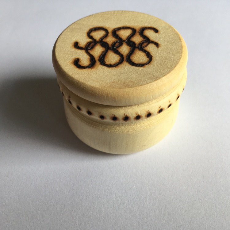 A picture of a large stitch marker pot with knitted stitches burnt into the lid and dots around the neck.