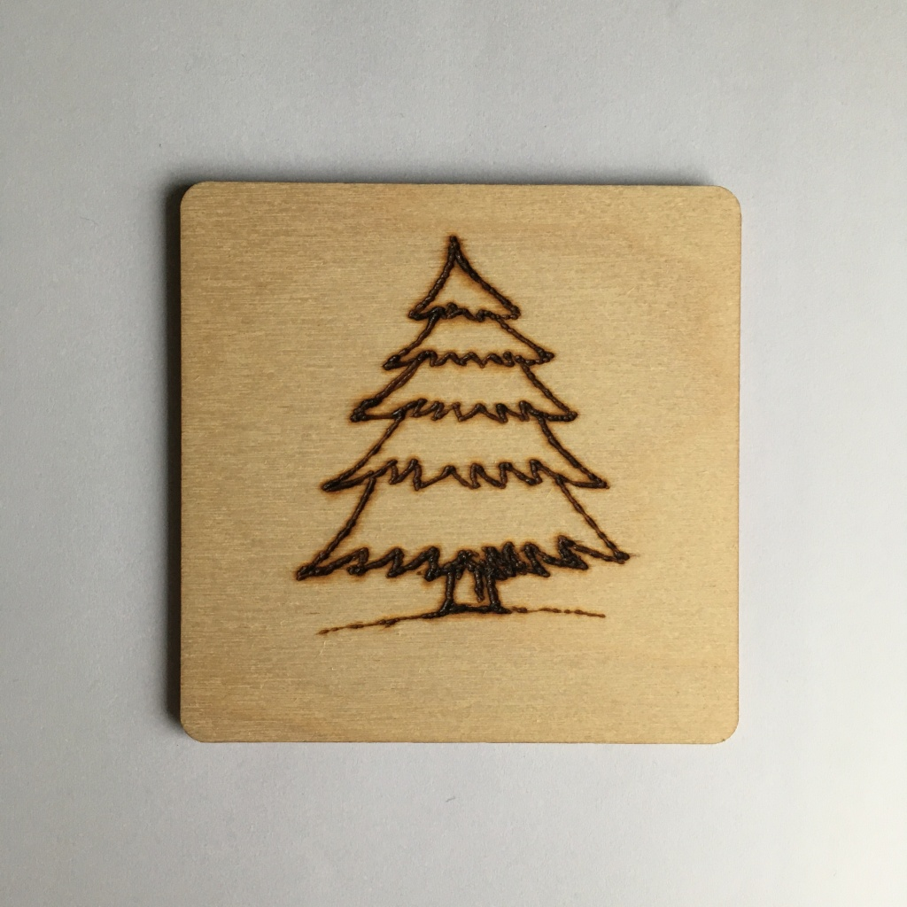 A picture of a square coaster with a Christmas tree burnt onto it.