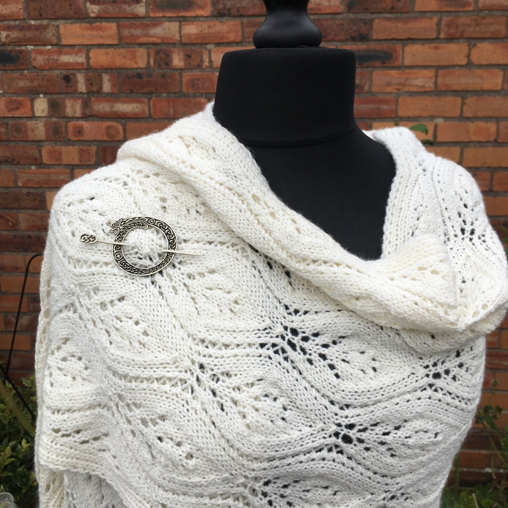 A picture of Ogee Lace Scarf or Wrap shown on a mannequin with a shawl pin.