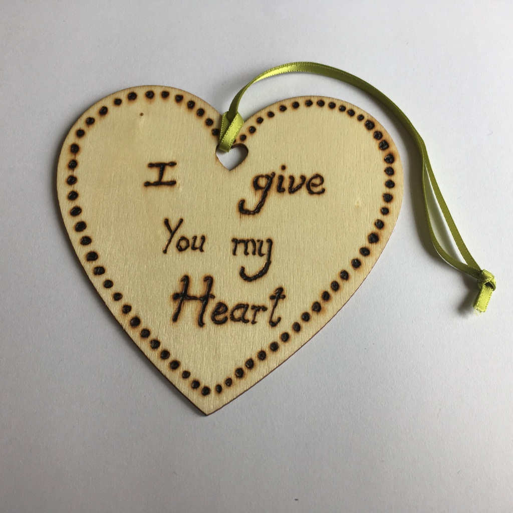 A picture of a hanging heart decoration with the words 'I give You my Heart' and dots all around the edge burnt onto it.