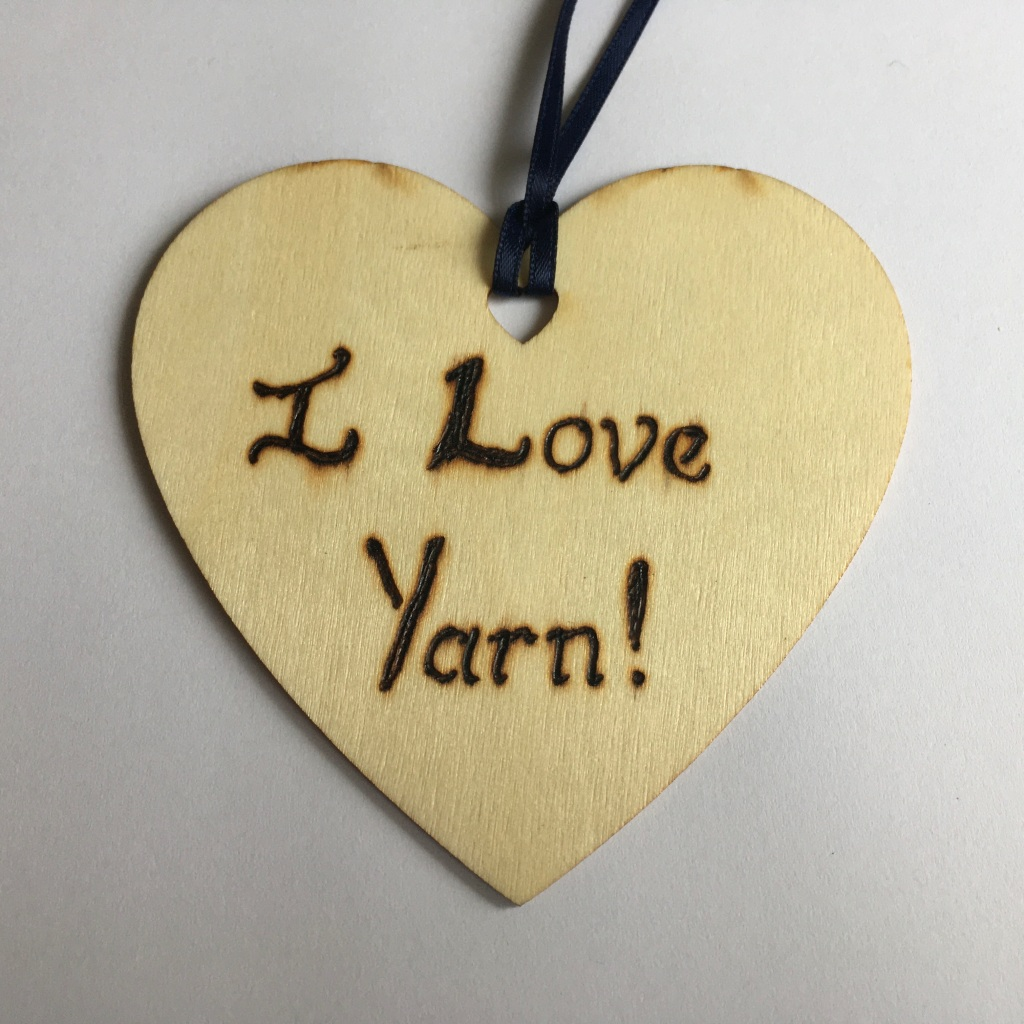 A picture of a hanging heart decoration with the words 'I Love Yarn!' burnt onto it.