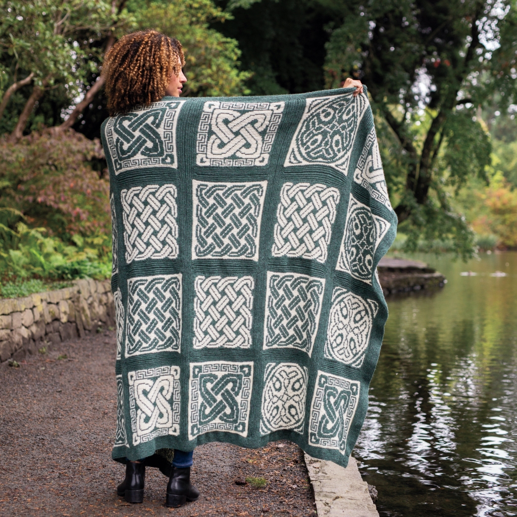 A picture of Nevern Throw wrapped around a model and held out. Photo copyright to Knit Picks.