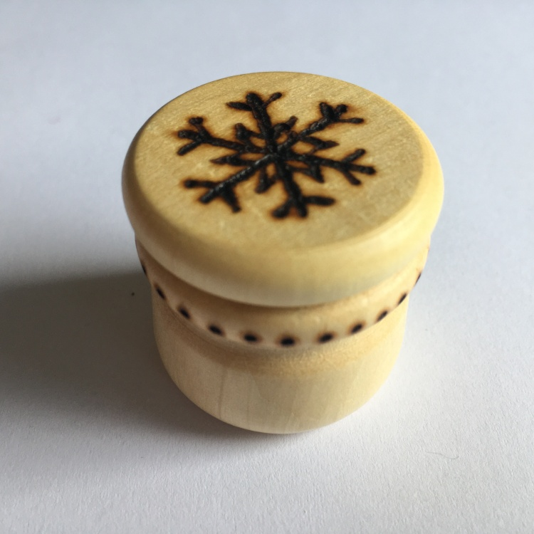A picture of a small stitch marker pot with a snowflake burnt into the lid and dots around the neck.