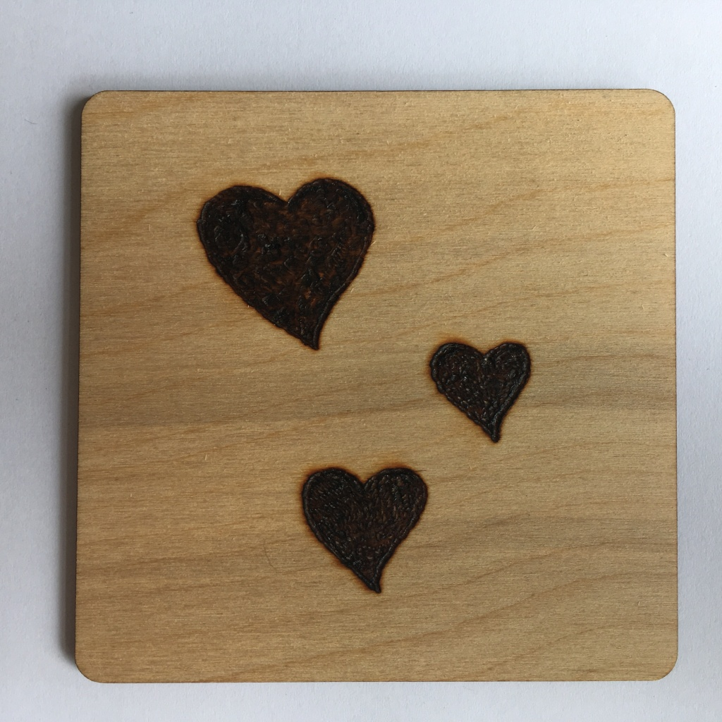 A picture of a square coaster with three small to medium filled hearts burnt onto it.
