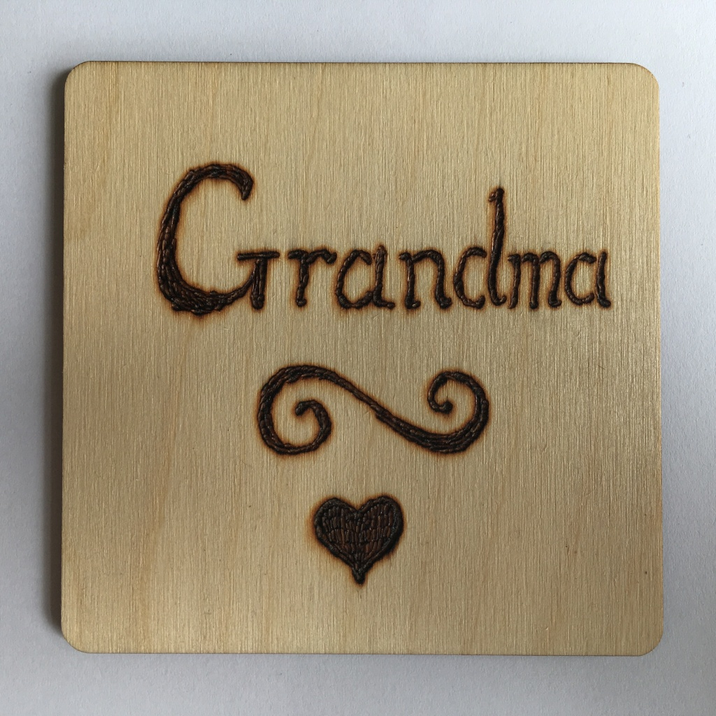 A picture of a square coaster with the word 'Grandma' burnt onto it. Underneath is a scroll and a small filled heart.