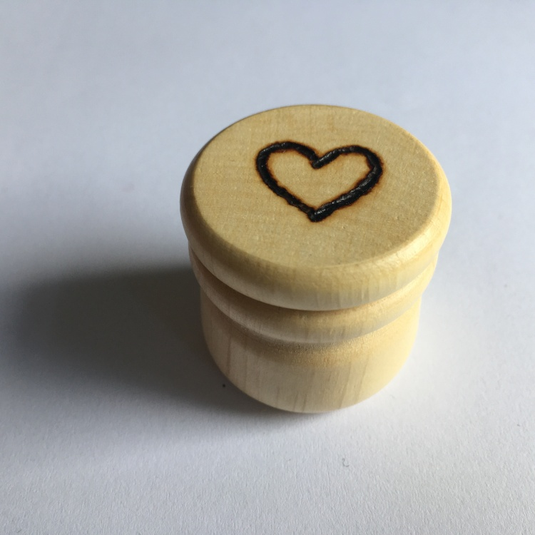 A picture of a small stitch marker pot with a heart outline burnt into the lid.