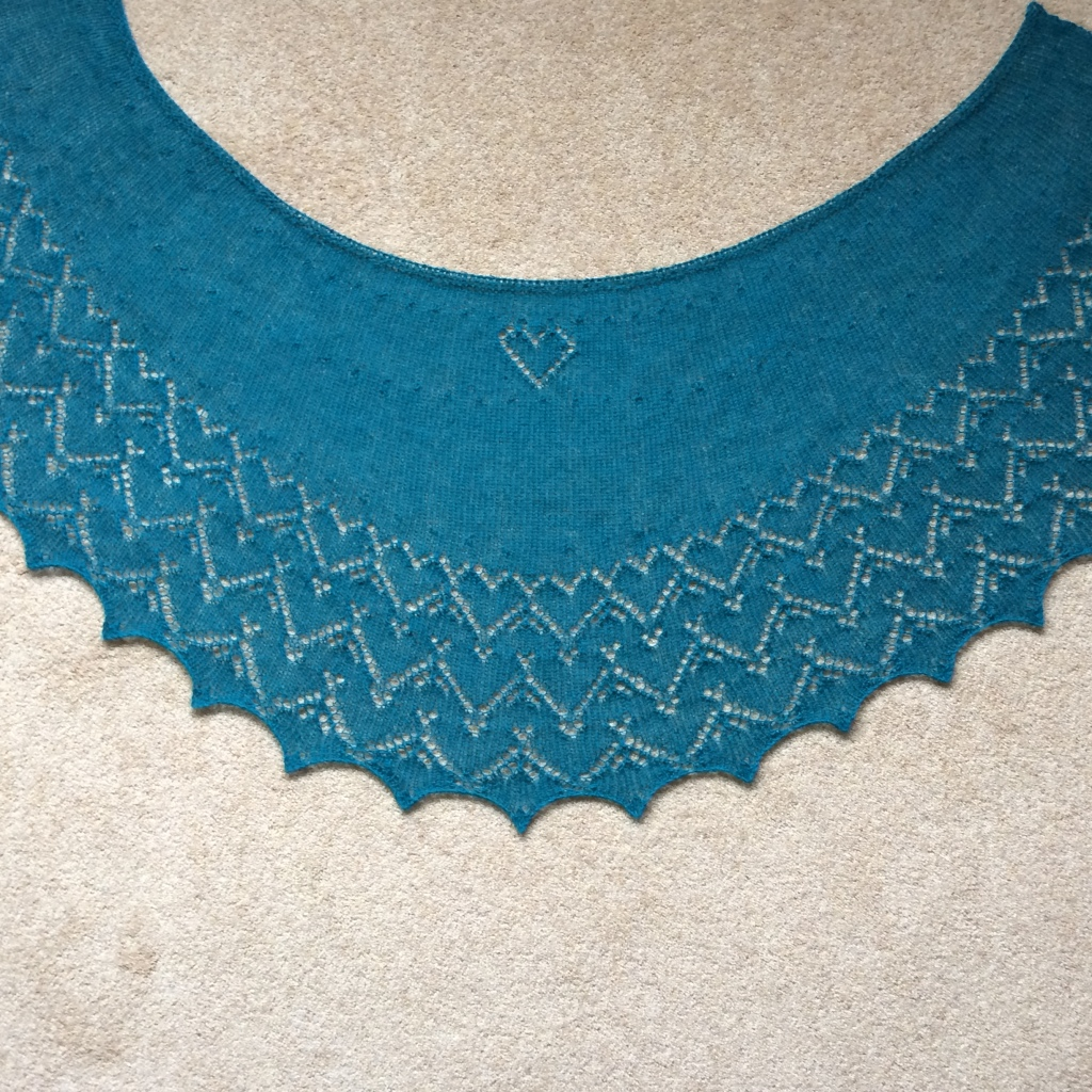 A picture of Calon Cariad Shawl spread out on a flat surface.