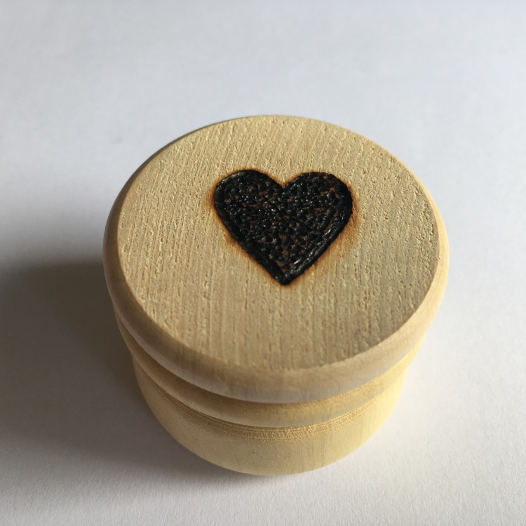 A picture of a large stitch marker pot with a filled heart burnt into the lid.