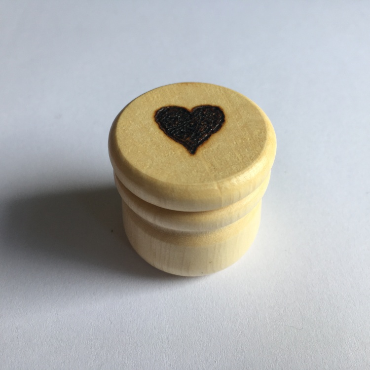 A picture of a small stitch marker pot with a filled heart burnt into the lid.