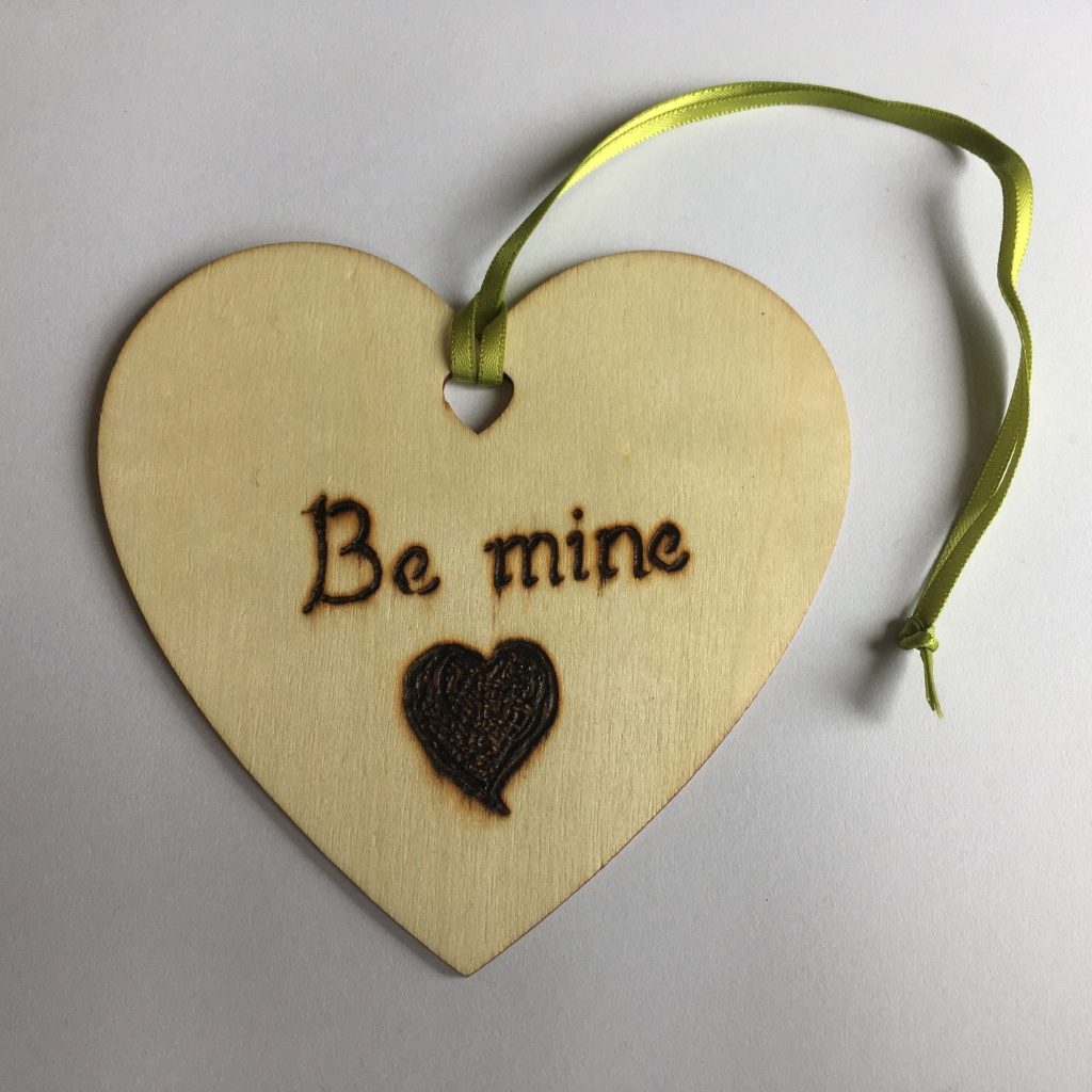 A picture of a hanging heart decoration with the words 'Be mine!' and a medium filled heart burnt onto it.