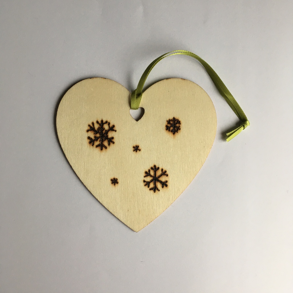A picture of a hanging heart decoration with three large, one medium and two small snowflakes burnt onto it.