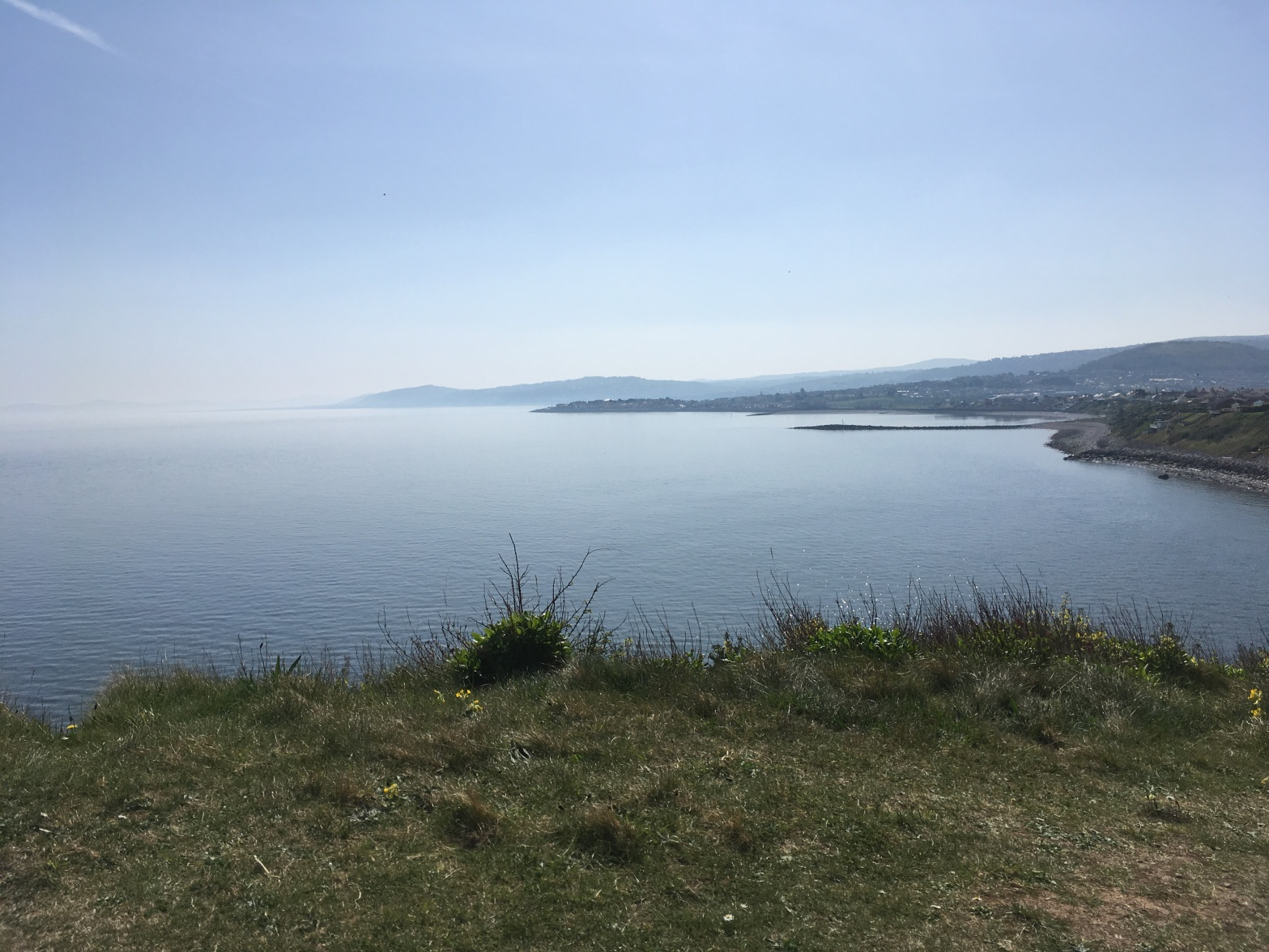 A view from the top of the Little Orme towards Penrhyn Bay and Rhos-on-Sea. The sea is calm and the sky has a few hazy clouds.
