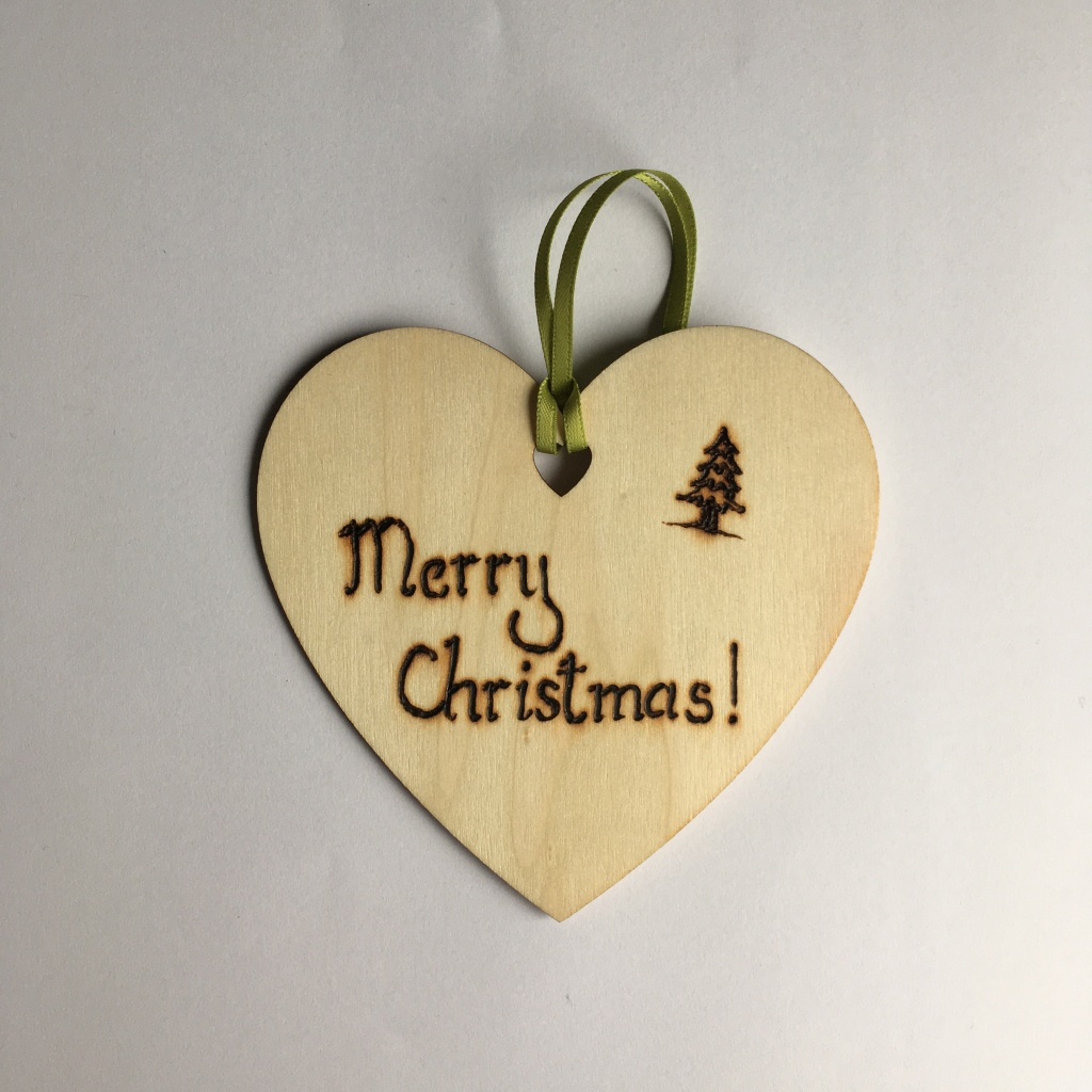 A picture of a hanging heart decoration with the words 'Marry Christmas!' and a small Christmas tree burnt onto it.