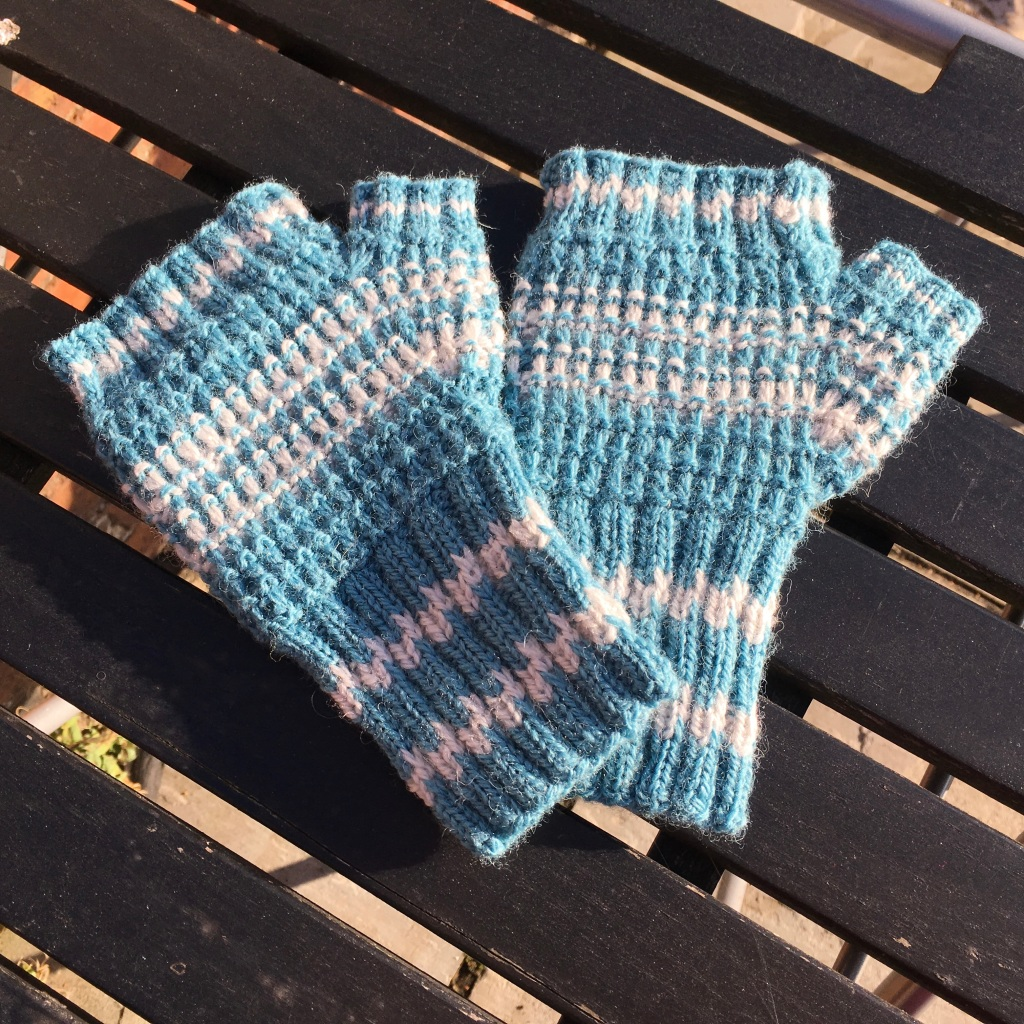 A picture of Nubble Slip Stitch Mitts on a slatted table.