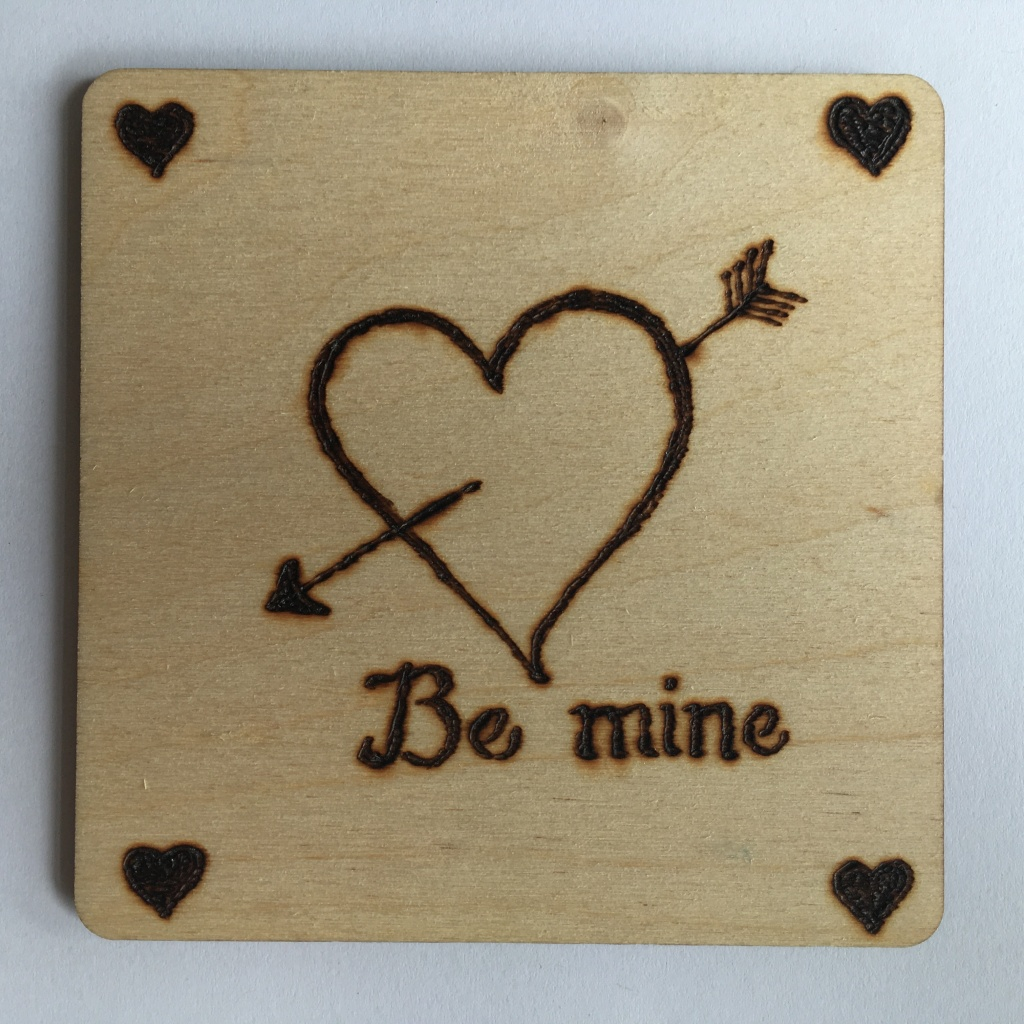 A picture of a square coaster with a large heart outline and an arrow going through burnt onto it. The words 'Be mine' are underneath and there is a small filled heart in each corner.