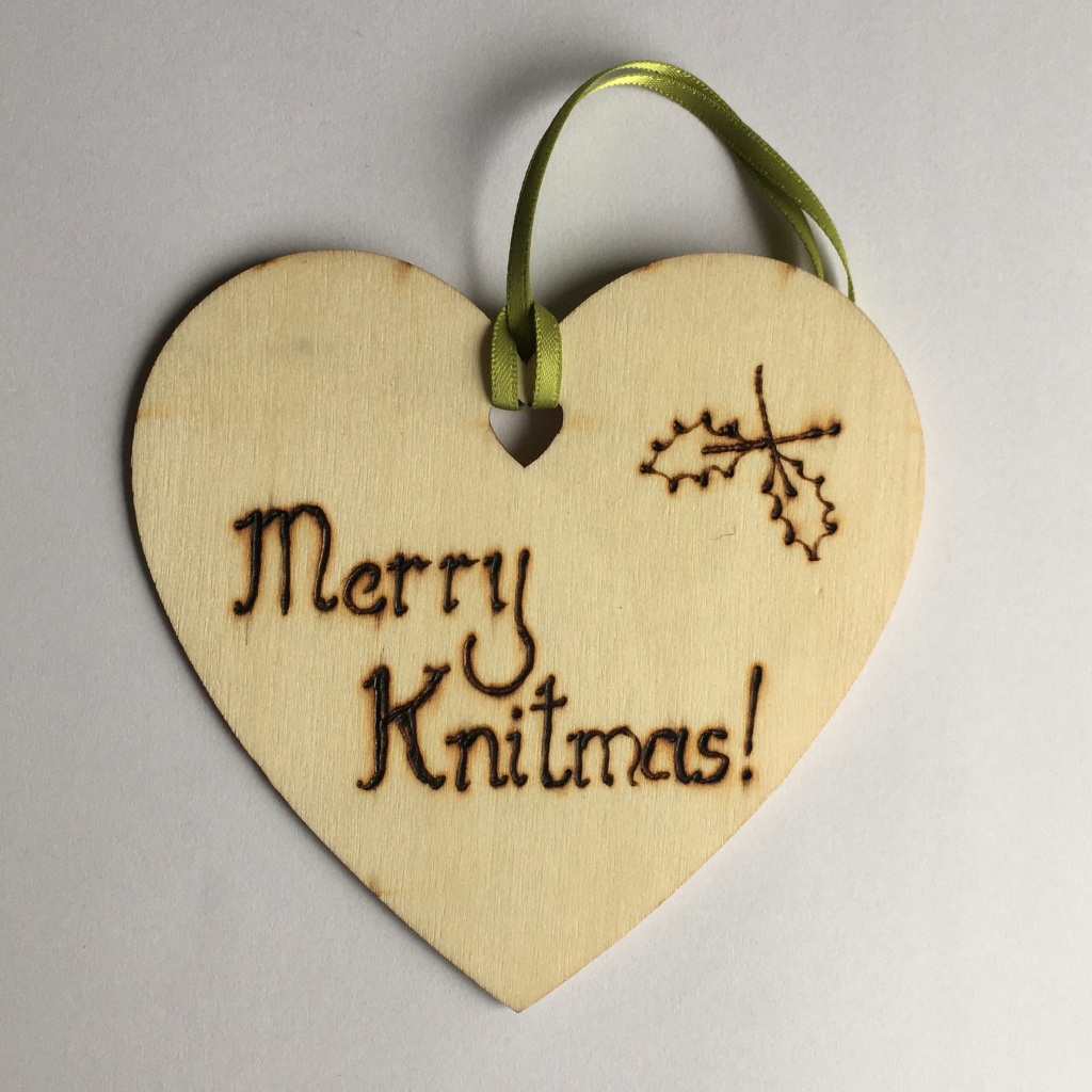 A picture of a hanging heart decoration with the words 'Merry Knitmas!' and a medium pair of holly leaves burnt onto it.