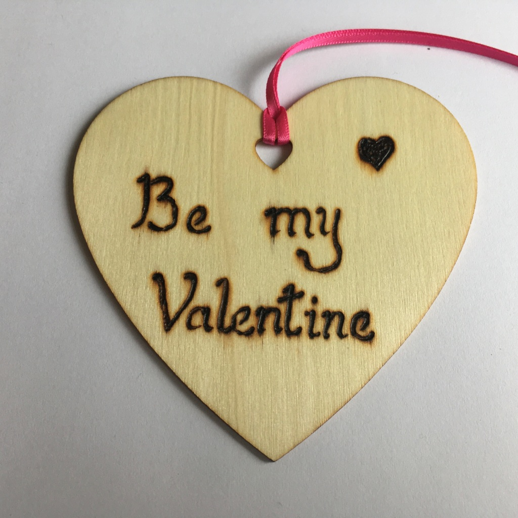 A picture of a hanging heart decoration with the words 'Be my Valentine' and a small filled heart burnt onto it.