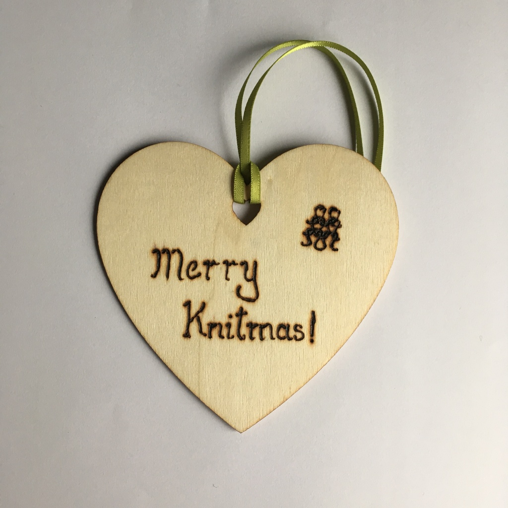 A picture of a hanging heart decoration with the words 'Merry Knitmas!' and some knitted stitches burnt onto it.