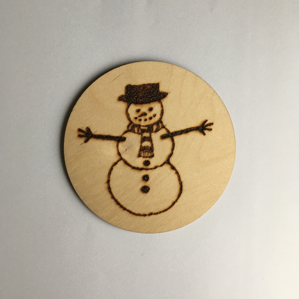 A picture of a round coaster with a snowman wearing a hat and scarf burnt onto it.