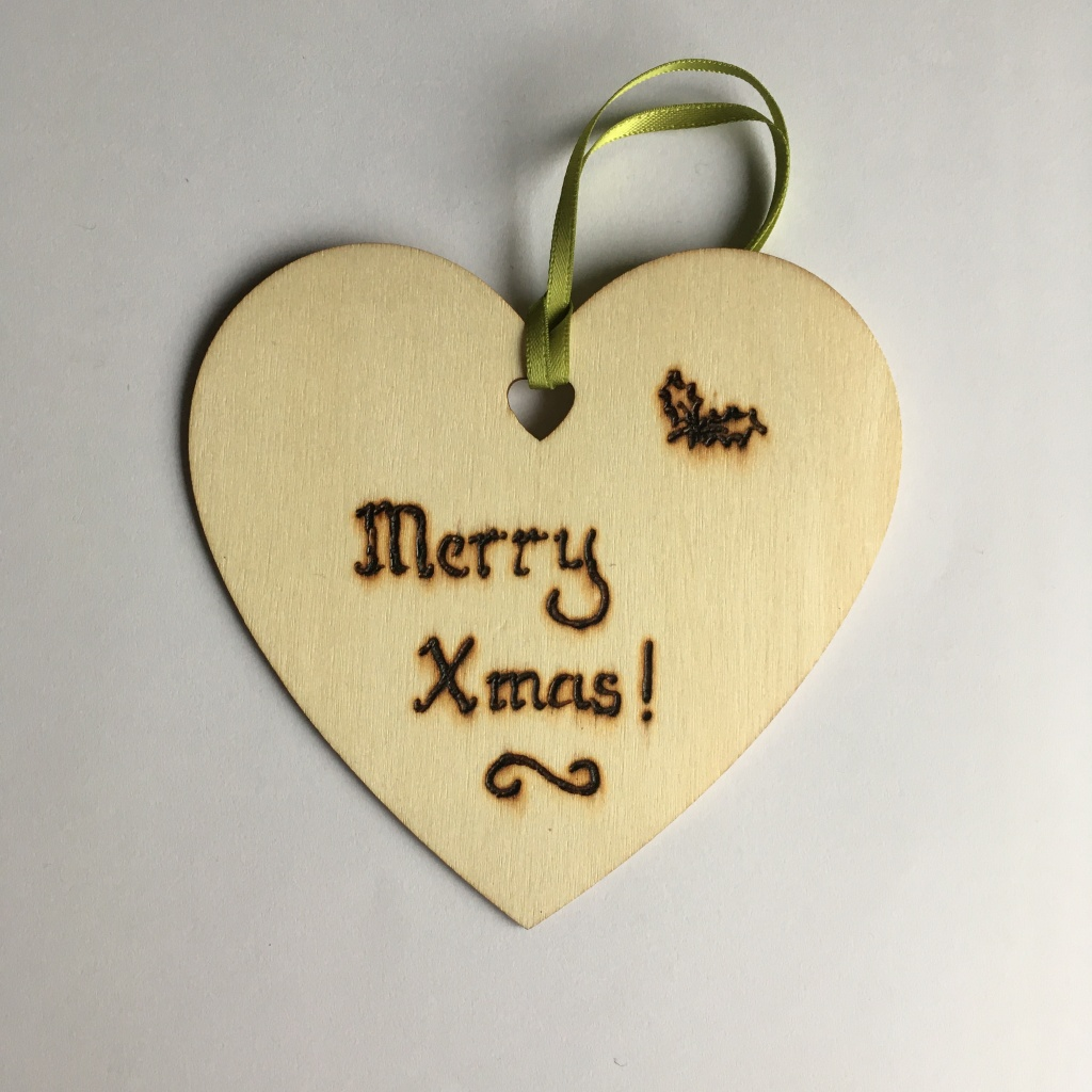 A picture of a hanging heart decoration with the words 'Merry Xmas!' and a small pair of holly leaves burnt onto it.