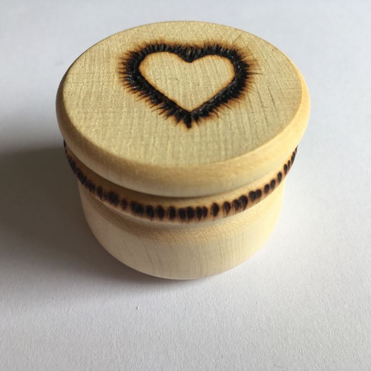 A picture of a large stitch marker pot with a feathered heart outline burnt into the lid and vertical lines around the neck.