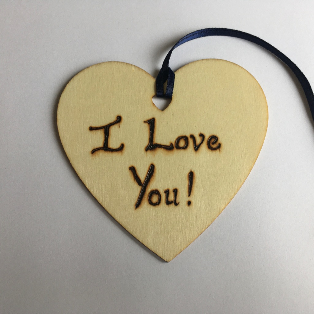 A picture of a hanging heart decoration with the words 'I Love You!' burnt onto it.