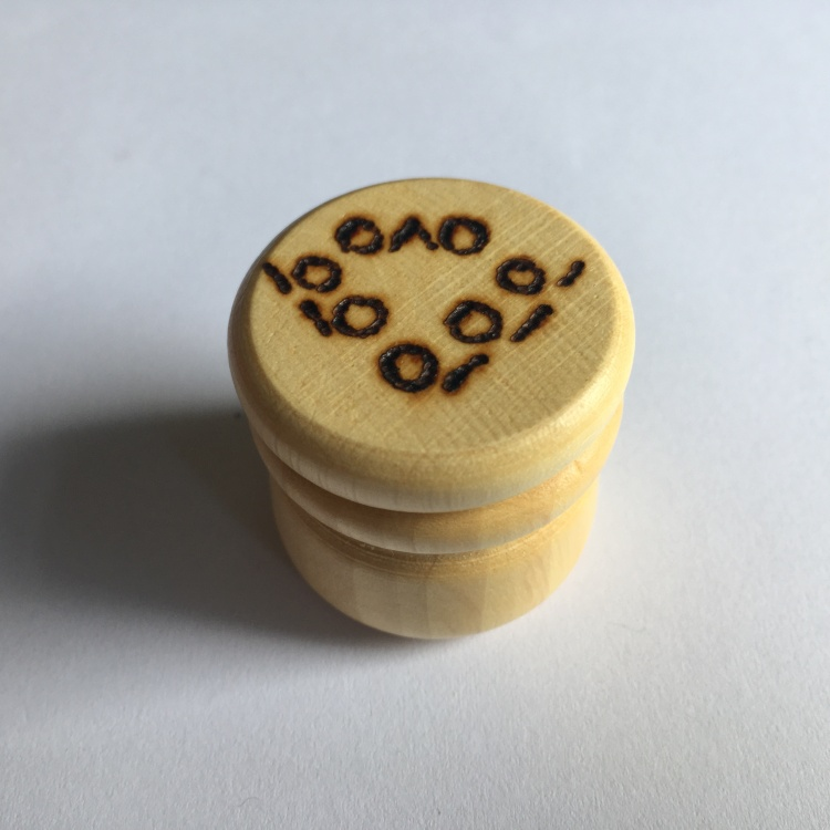 A picture of a small stitch marker pot with a lace chart burnt into the lid.
