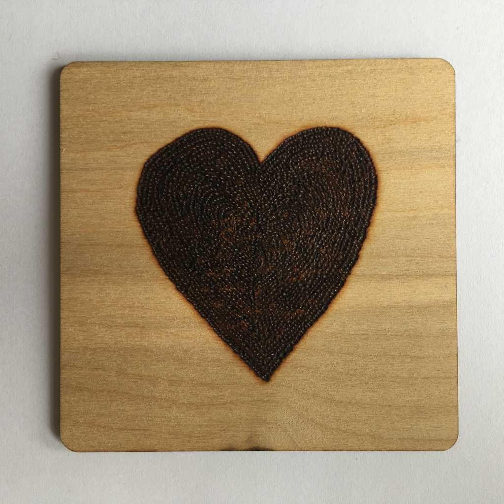 A picture of a square coaster with a large filled heart burnt onto it.