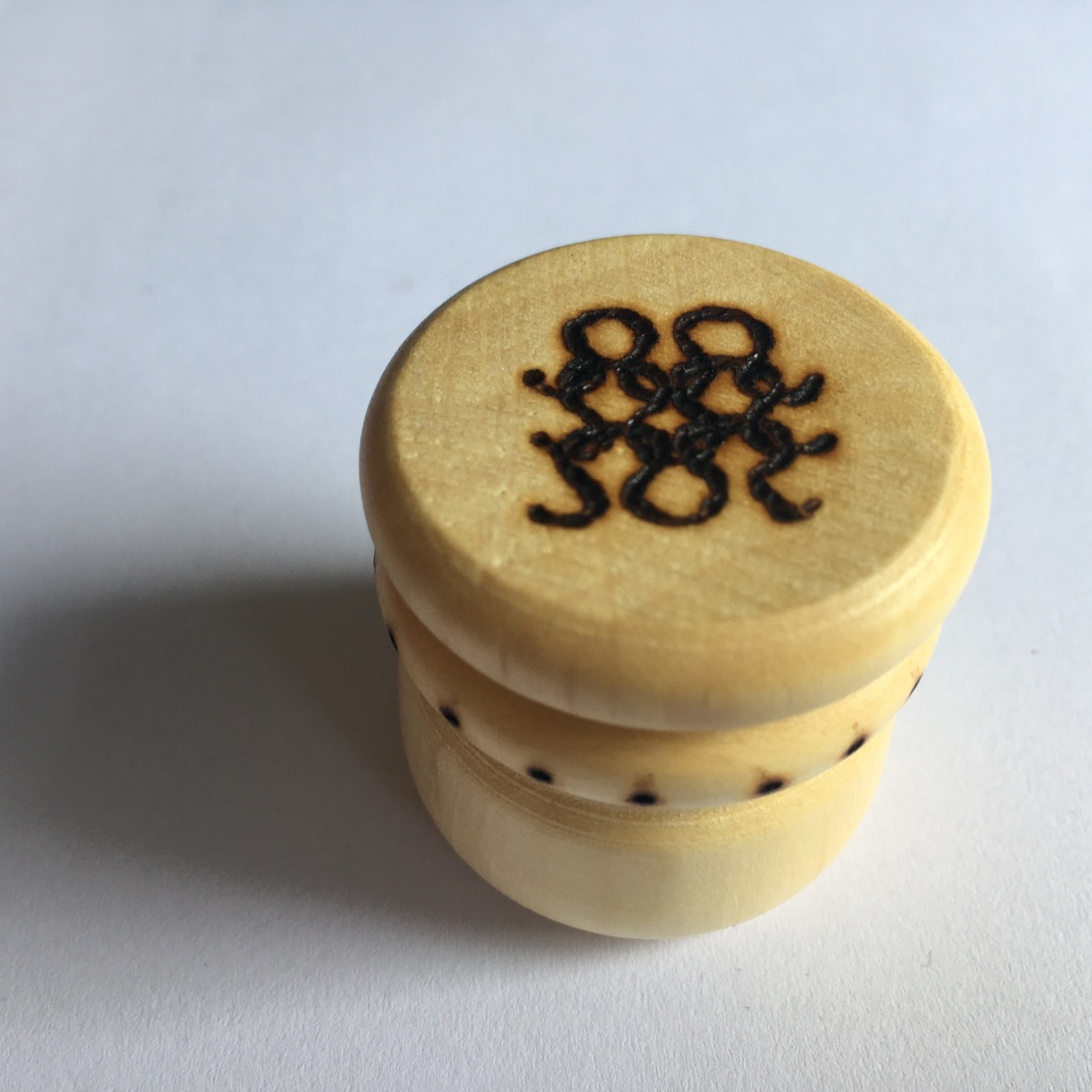 A picture of a small stitch marker pot with knitted stitches burnt into the lid and dots around the neck.