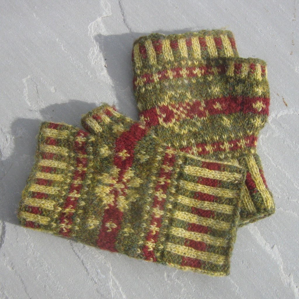 A picture of Heart in my Hands Mitts laid on a flat surface showing the different designs on back and palm.