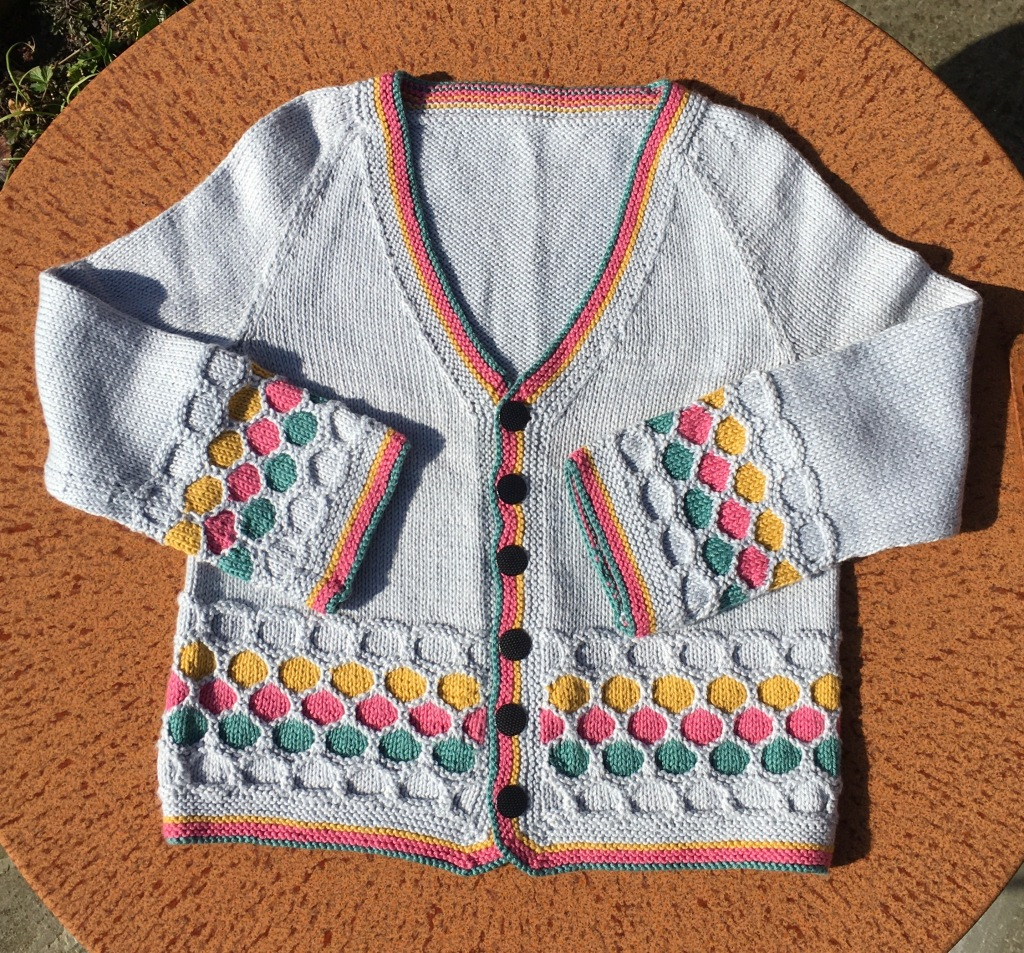 A picture of Honeybun Cardigan laid on a flat surface.