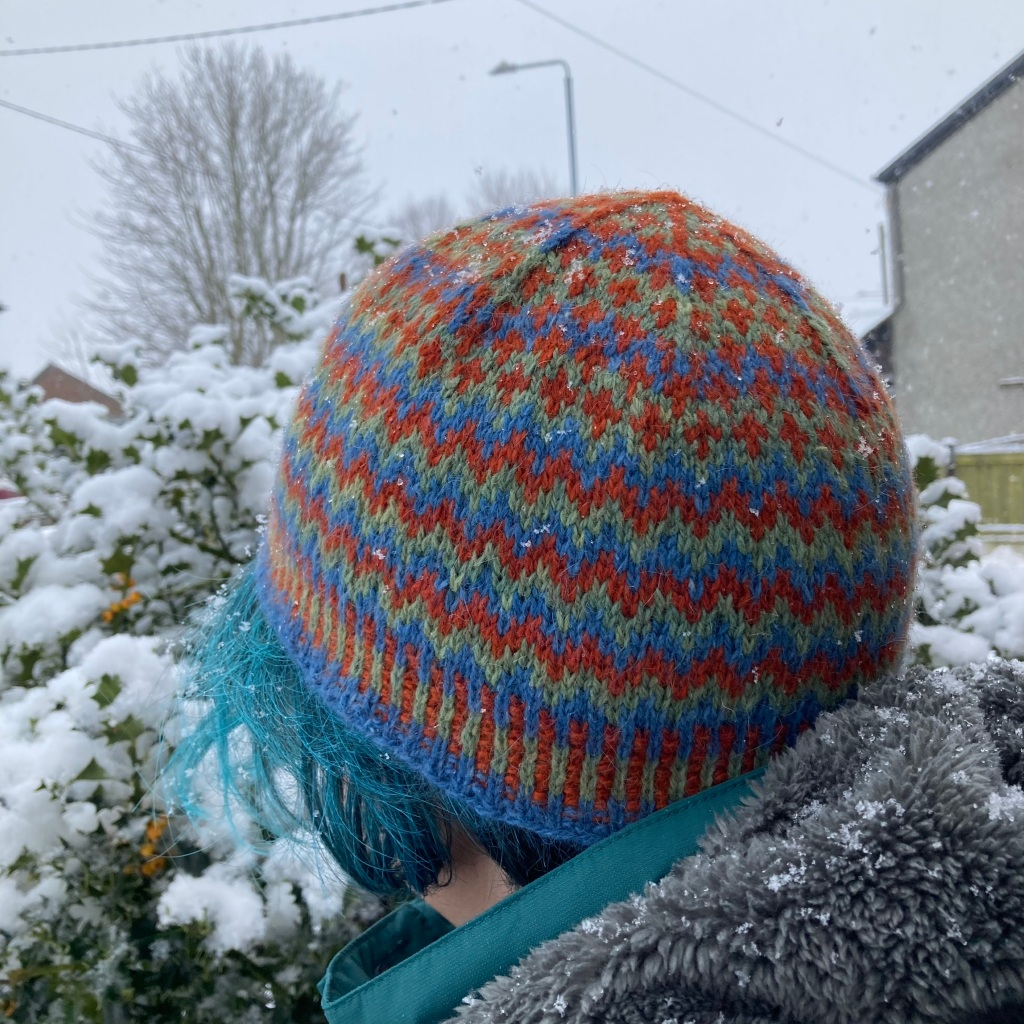 A woman standing in the snow, looking away from the camera wearing an orange, blue and green hat (Llanberis Hat).
