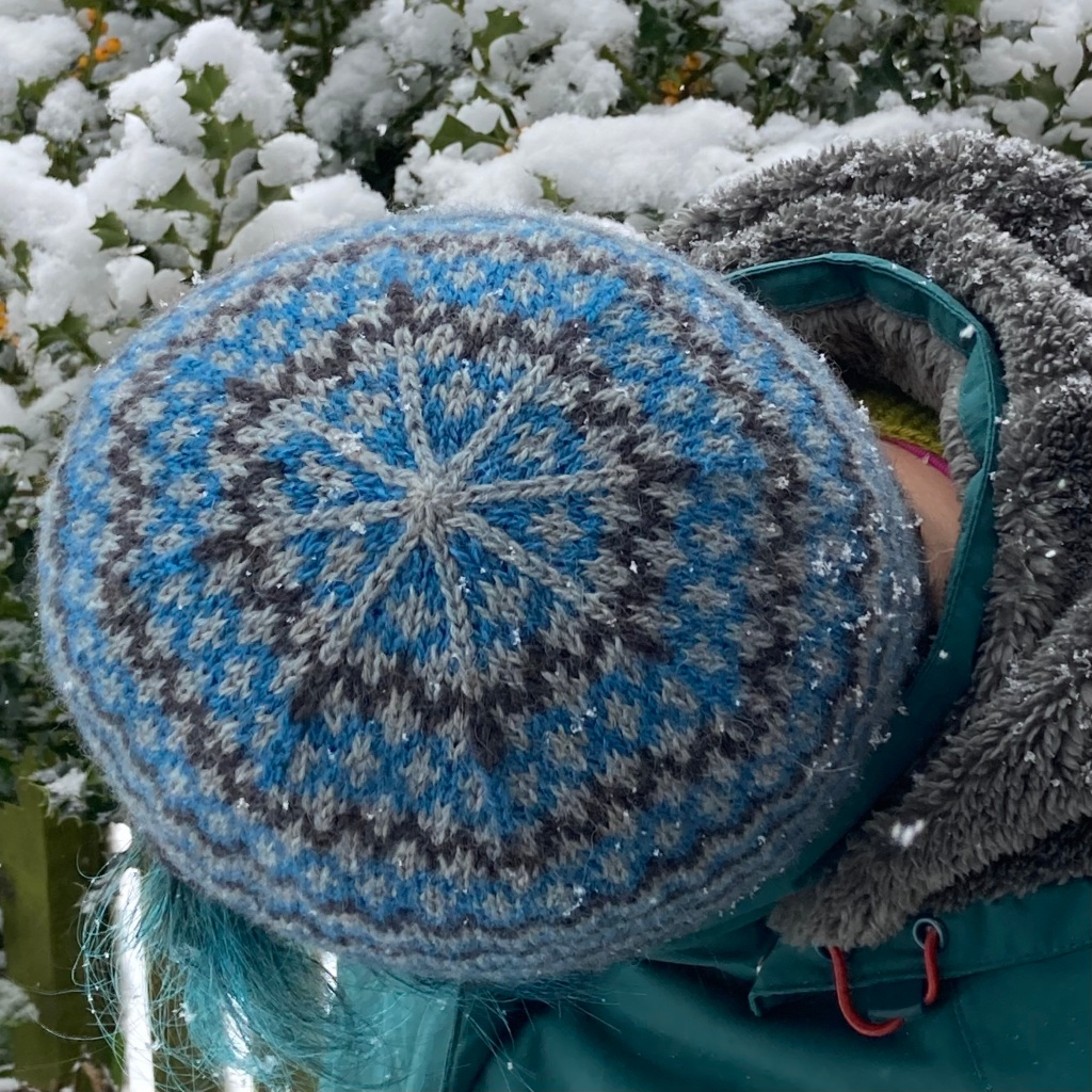 A woman standing in the snow, bending sideways to show the crown of her blue, silver and grey knitted hat (Llanberis Hat)
