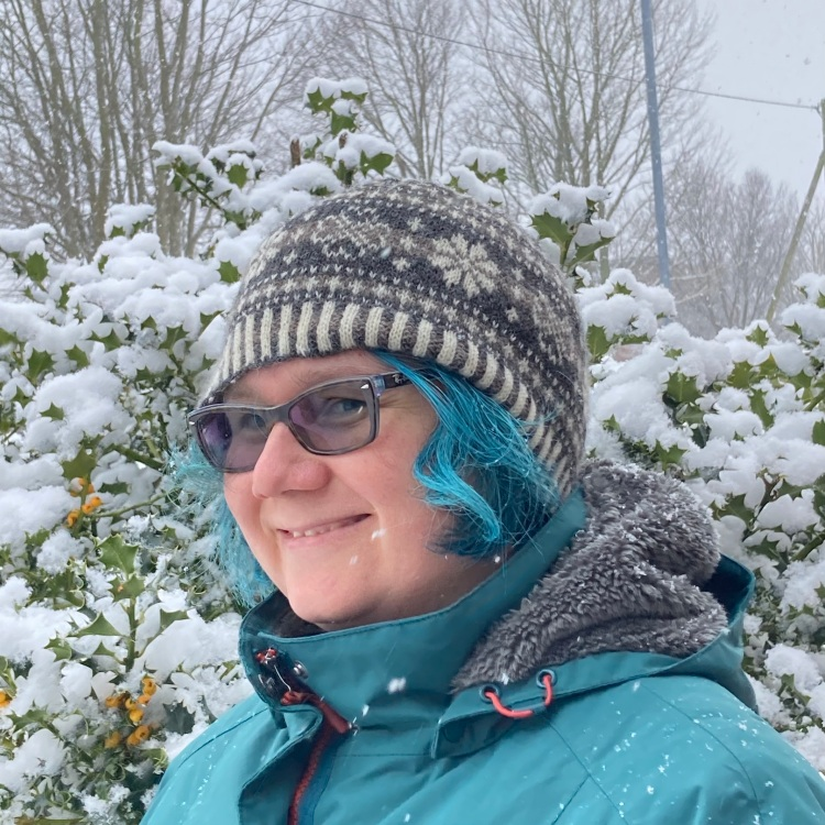 Woman with blue hair and coat standing in front of snowy holly bush wearing knitted Fair Isle hat