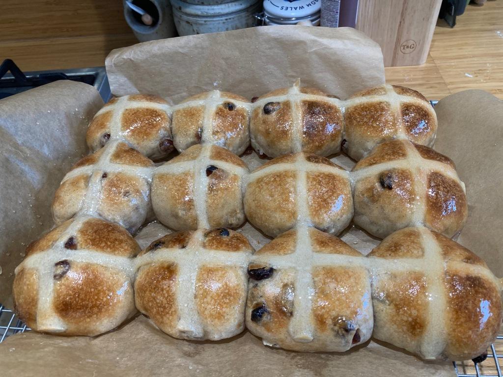 A dozen homemade hot cross buns sitting on baking parchment.