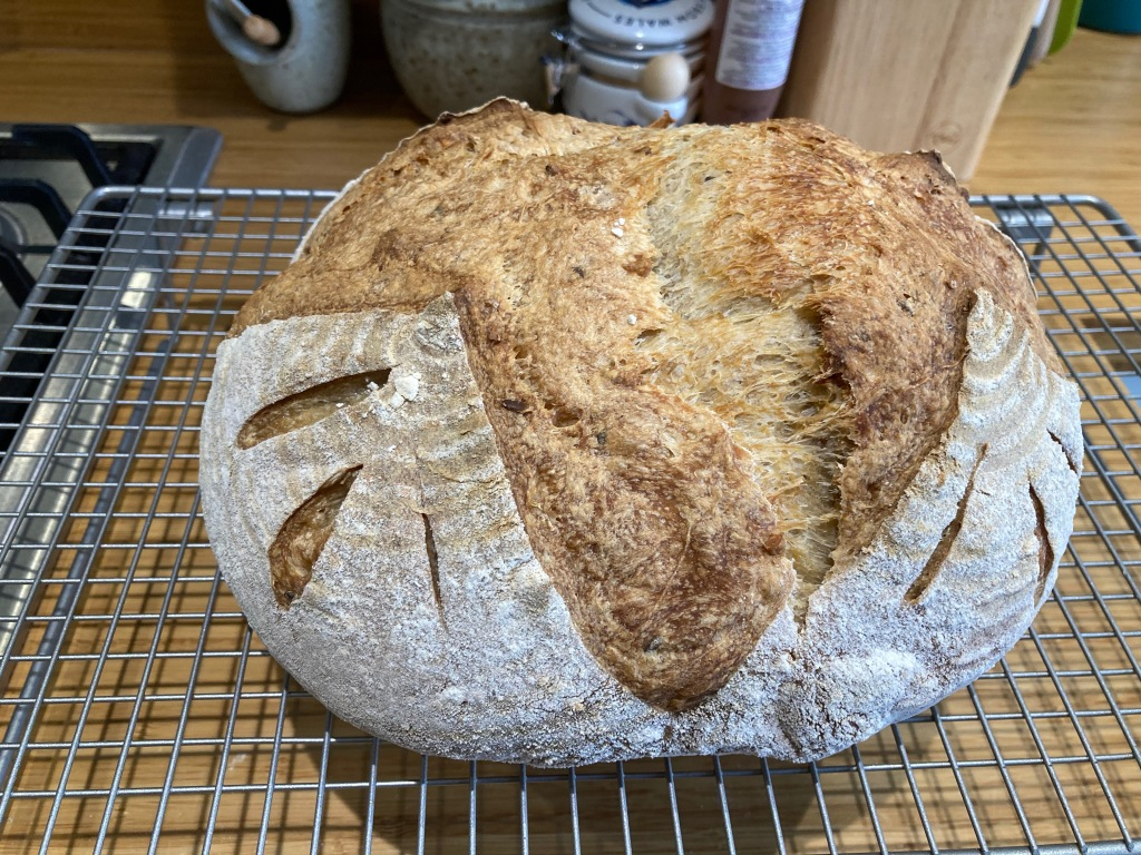 A well-risen sourdough loaf on a cooling rack.
