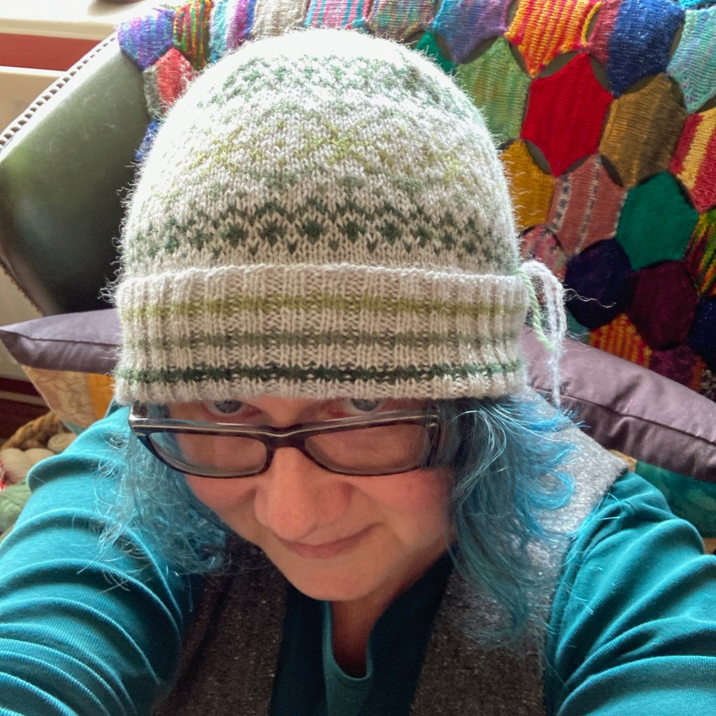 A blue-haired middle-aged woman (me) looks at the camera over her glasses wearing Little Orme Hat, a stranded colourwork hat with a striped folded brim. She is sitting in front of a patchwork blanket.