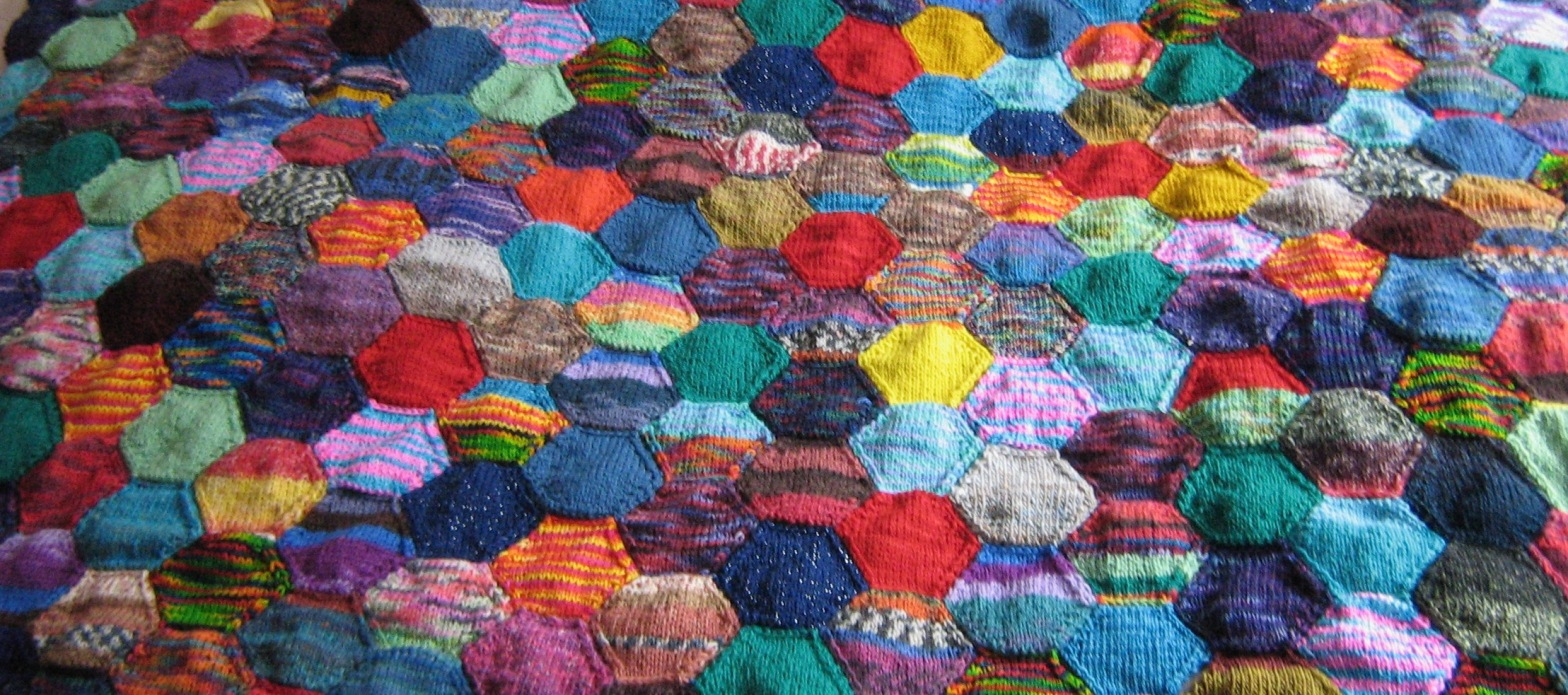 A close-up of knitted hexagons made from a random mix of leftover sock yarns