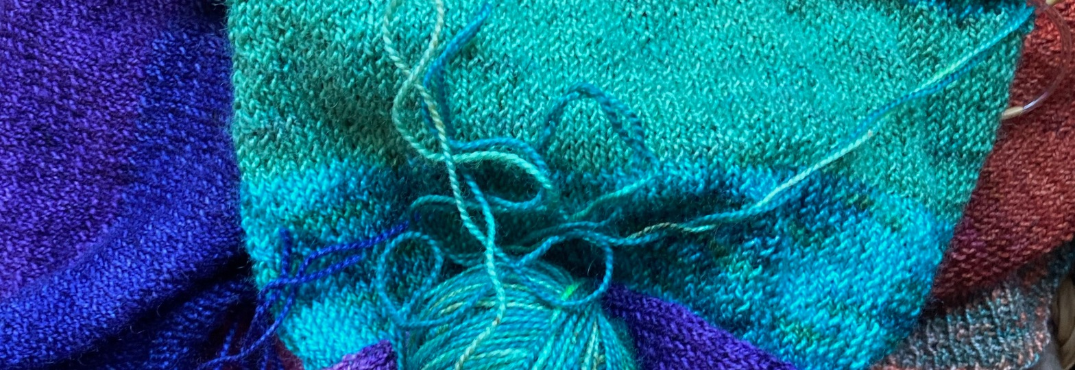 A close-up of turquoise, purple and blue knitting; part of a sweater in progress
