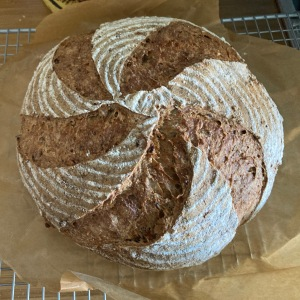 An overhead shot of a sourdough loaf scored with five lines spiralling to the centre