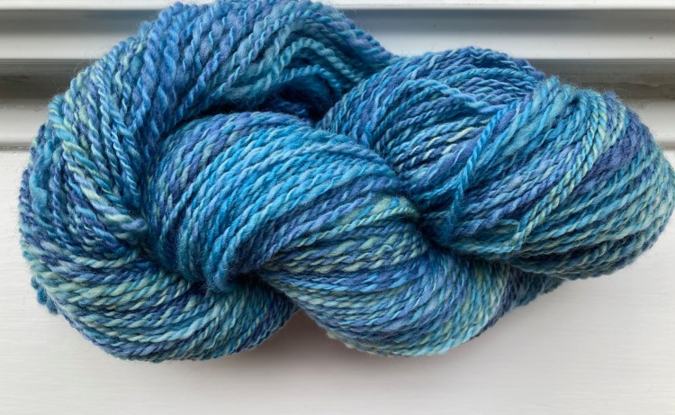 A handspun skein of Polwarth wool in shades on blue and sea-green on a white window-sill.
