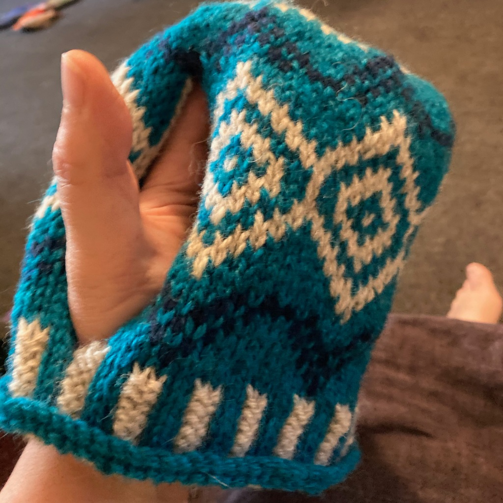 A stranded tea-cosy in teal, dark blue and natural cream is held up with my thumb emerging from the stetted hole for the teapot handle. The angle of the Nordic stranded knitting pattern gives the impression of a grumpy face.