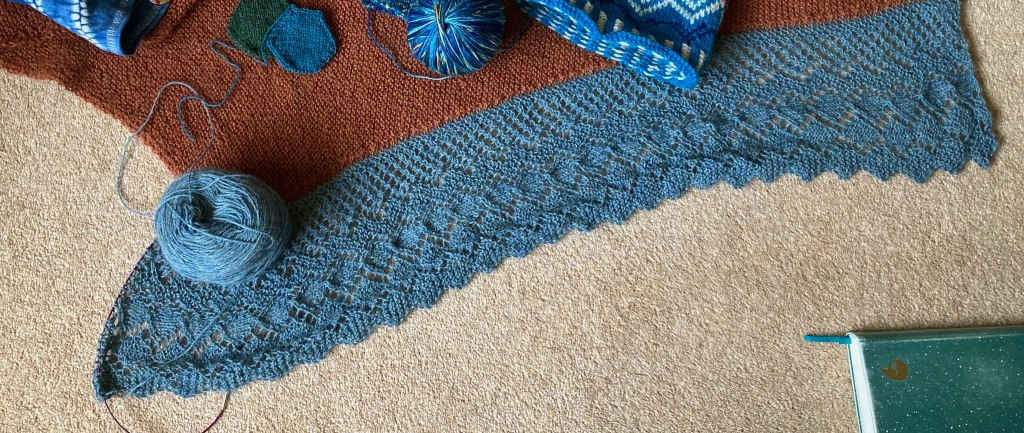 A copper garter stitch shawl is laid out on a pale carpet. The silver-blue deep lace edging is half completed. Other knitting projects sit on the garter stitch.