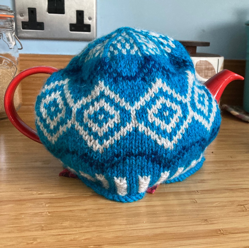 A bright blue Fair Isle tea cosy with dark blue and cream pattern sits on a red teapot on a bamboo kitchen worktop.